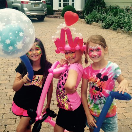 Face painting and balloon twisting for a girls